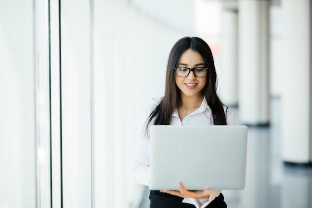 Portrait de jeune femme d'affaires travaillant tenant un ordinateur portable debout contre une fenêtre panoramique avec vue sur la ville