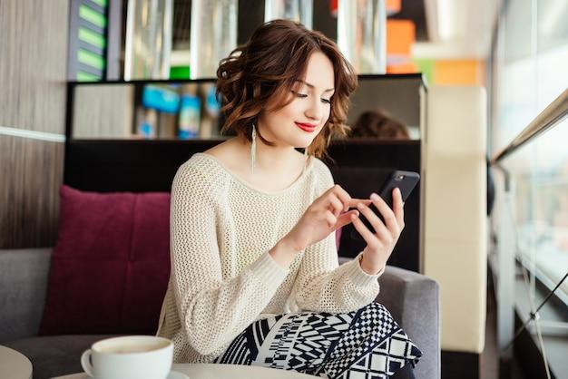 Portrait de jeune femme d'affaires utilise un téléphone mobile tout en étant assis dans un café confortable