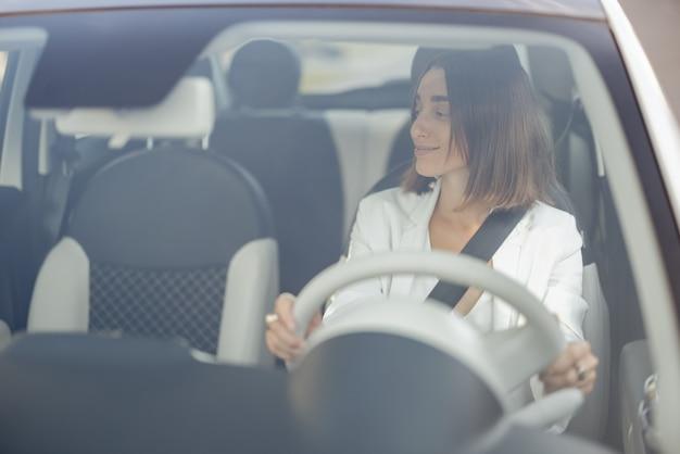 Portrait d'une jeune femme d'affaires vêtue d'un costume blanc au volant d'une voiture, vue à travers le pare-brise