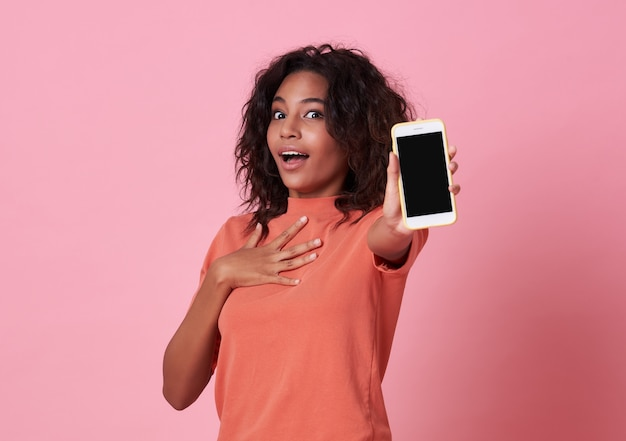 Portrait d'une jeune femme africaine excitée montrant au téléphone mobile à écran blanc isolé sur rose.