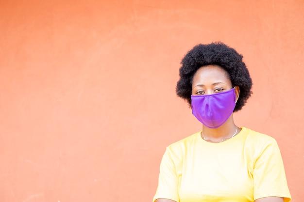 Portrait d'une jeune femme africaine heureuse porter un masque facial fait maison