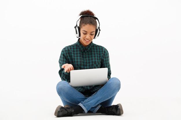 Portrait de jeune femme africaine avec ordinateur portable sur blanc