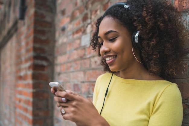 Portrait de jeune femme afro-américaine à l'aide de téléphone portable et écouter de la musique avec des écouteurs dans la rue.