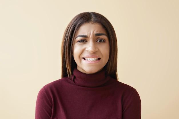 Portrait de jeune femme afro-américaine brune dégoûtée frustrée fronçant les sourcils et grimaçant à cause d'une odeur dégoûtante ou puante, serrant les dents. mauvaise odeur, dégoût et émotions négatives