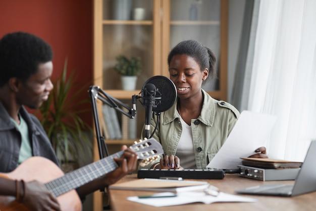 Portrait de jeune femme afro-américaine chantant au micro tout en enregistrant de la musique en home studio, espace copie