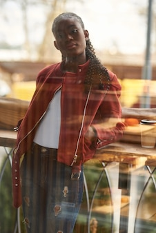 Portrait de jeune femme afro-américaine debout sur un balcon portant un jean et une veste rouge