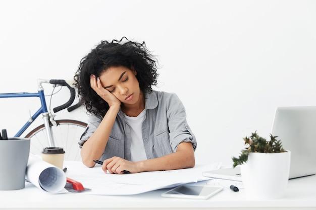 Portrait de jeune femme afro-américaine fatiguée, décorateur d'intérieur, oreiller tête sur place