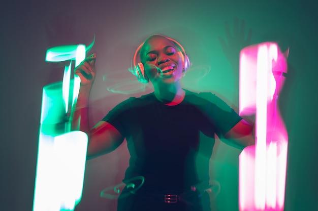 Portrait de jeune femme afro-américaine sur fond dégradé. beau modèle féminin dansant, chantant dans des néons délicieux. concept d'émotions humaines, expression faciale, ventes, publicité, inclusion.
