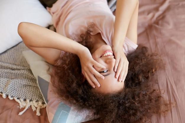 Portrait de jeune femme afro-américaine heureuse allongée sur le lit et le visage contre avec les mains, profitez de la journée ensoleillée à la maison et souriant.