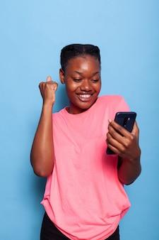 Portrait d'une jeune femme afro-américaine heureuse a reçu un message d'un ami