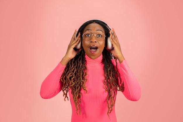 Portrait de jeune femme afro-américaine isolée sur fond de studio rose, expression faciale.