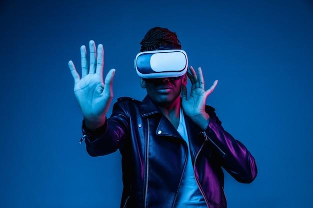 Portrait de jeune femme afro-américaine jouant dans des lunettes vr en néon sur bleu.