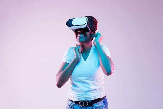 Portrait de jeune femme afro-américaine jouant dans des lunettes vr en néon sur fond dégradé
