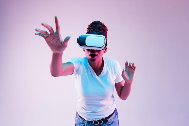 Portrait de jeune femme afro-américaine jouant dans des lunettes vr en néon sur gradient.