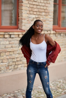 Portrait d'une jeune femme afro-américaine marchant dans la rue vêtue d'un jean et d'une veste rouge