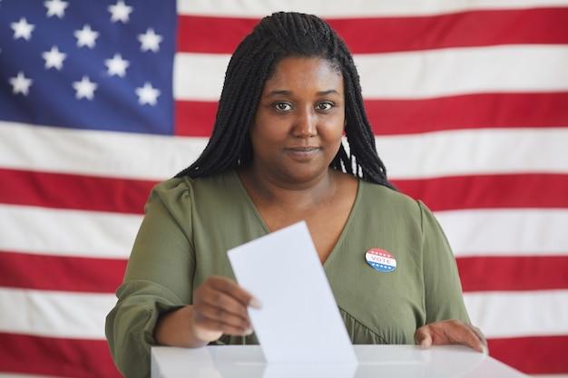 Portrait de jeune femme afro-américaine mettant bulletin de vote dans l'urne et en se tenant debout contre le drapeau américain le jour de l'élection, copiez l'espace