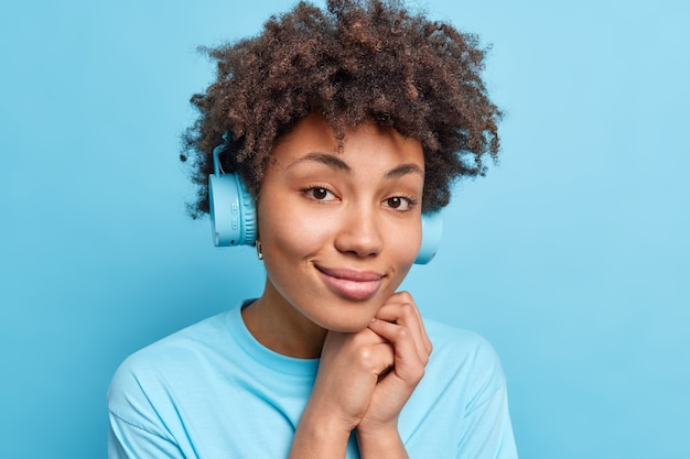 Portrait d'une jeune femme afro-américaine naturelle et heureuse qui sourit doucement et porte des écouteurs aime écouter de la musique, garde les mains près du visage isolé sur le mur bleu concept de passe-temps de loisirs de personnes