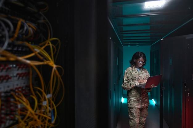 Portrait d'une jeune femme afro-américaine portant un uniforme militaire utilisant un ordinateur portable tout en se tenant dans la salle des serveurs, espace pour copie