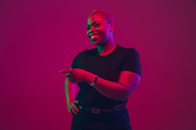 Portrait de jeune femme afro-américaine sur rose violet en néon