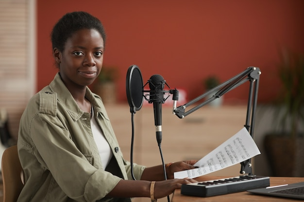 Portrait de jeune femme afro-américaine souriant à la caméra tout en composant de la musique en studio d'enregistrement à domicile, espace copie