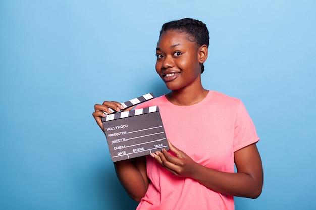 Portrait d'une jeune femme afro-américaine souriante tenant un tableau noir de production de film