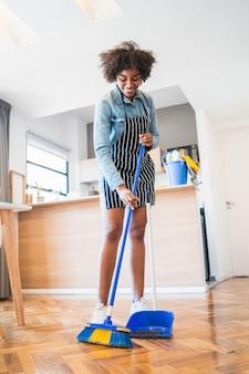 Portrait de jeune femme afro balayant le plancher en bois avec balai à la maison