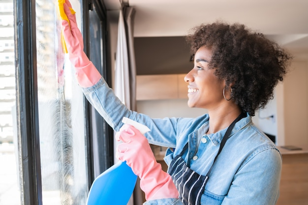 Portrait de jeune femme afro dans la fenêtre de nettoyage des gants avec un chiffon à la maison. concept de travaux ménagers, d'entretien ménager et de nettoyage.