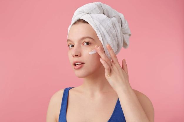 Portrait de jeune femme agréable avec une beauté naturelle après la douche avec une serviette sur la tête, souriant, à la recherche et met de la crème pour le visage.