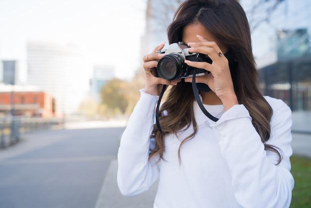 Portrait de jeune femme à l'aide d'un appareil photo numérique professionnel tout en se tenant à l'extérieur dans la rue. concept de photographie