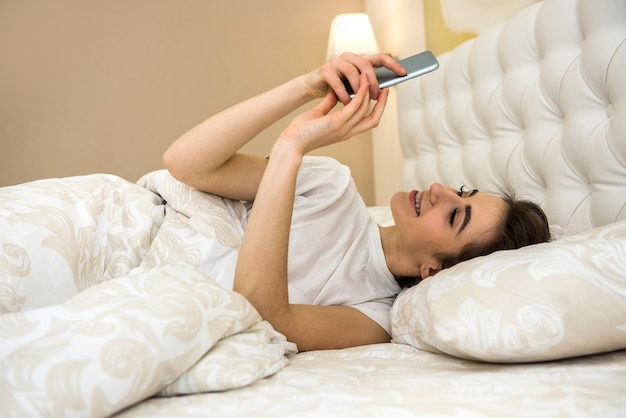 Portrait de jeune femme allongée sur le lit avec téléphone dans un appartement moderne le matin. problèmes de réveil ou de sommeil