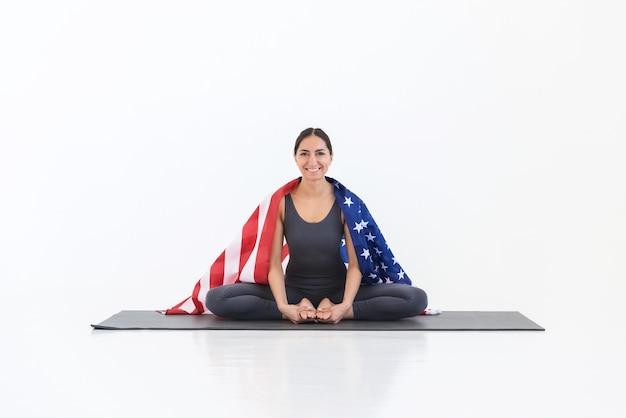 Portrait de jeune femme américaine heureuse pratiquant le yoga avec le drapeau américain sur fond blanc