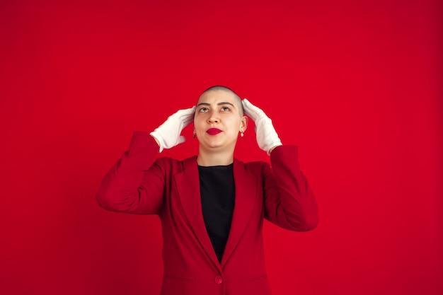 Portrait de jeune femme avec une apparence bizarre sur le mur rouge
