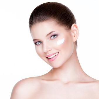 Portrait de jeune femme appliquant la crème sur son joli visage - sur fond blanc.