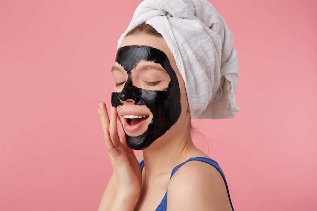 Portrait de jeune femme appréciant après la douche avec une serviette sur la tête, avec un masque noir, touche le visage, se dresse.
