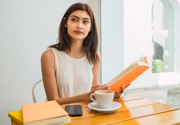 Portrait de jeune femme appréciant le temps libre et lisant un livre assis à l'extérieur au café.