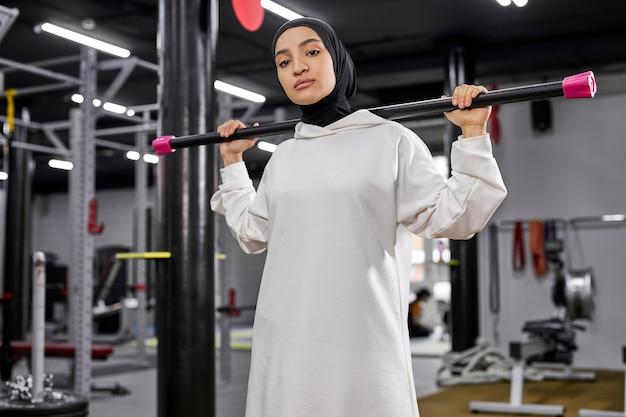 Portrait de jeune femme arabe exerçant avec des poids dans la salle de sport, elle se tient à la recherche de l'appareil photo, sérieux et confiant, portant le hijab sportif blanc