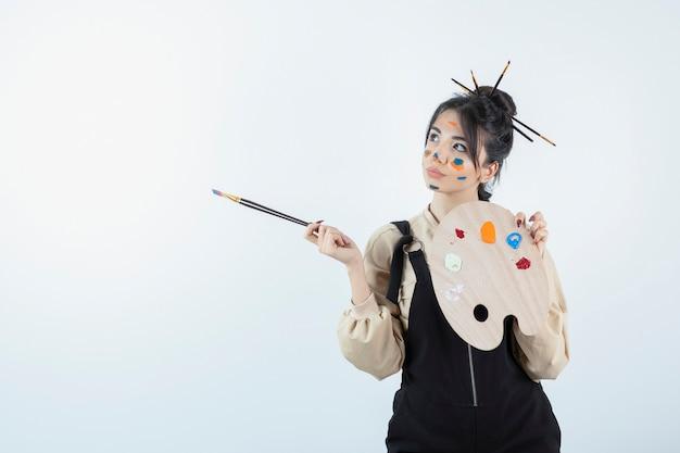 Portrait d'une jeune femme artiste posant avec un visage peint et tenant une palette en bois.