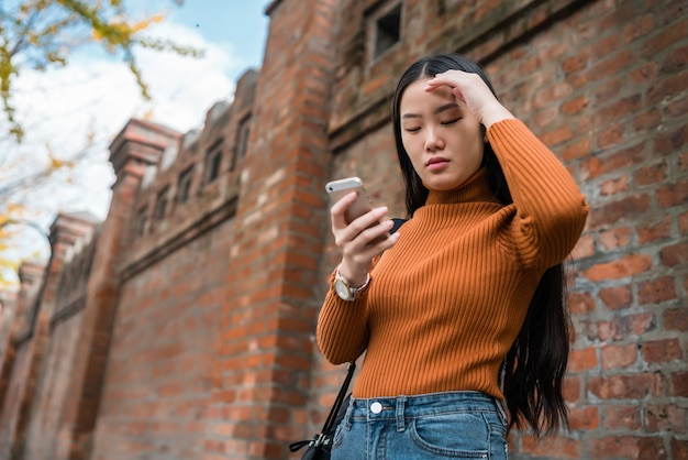 Portrait de jeune femme asiatique à l'aide de son téléphone portable dans la rue.