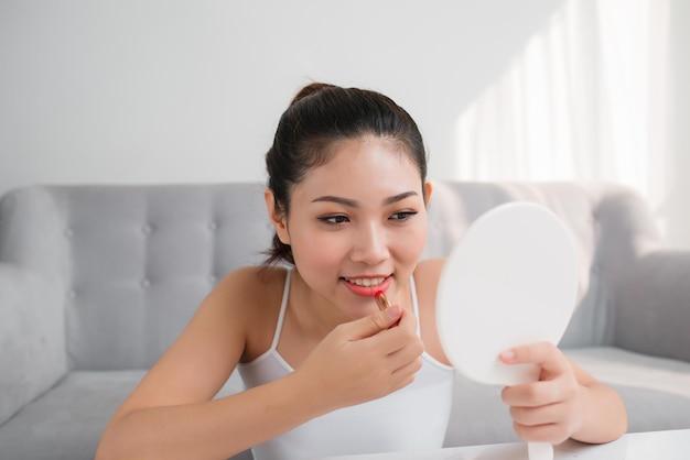 Portrait de jeune femme asiatique appliquant le rouge à lèvres regardant le miroir