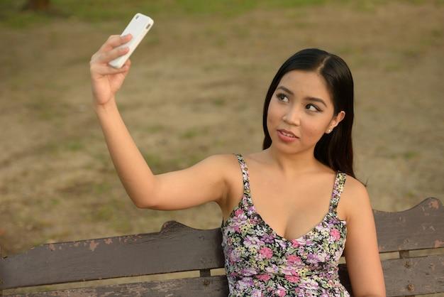 Portrait de jeune femme asiatique belle détente dans le parc en plein air