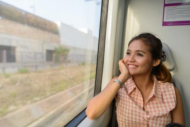 Portrait de jeune femme asiatique belle touriste assis à l'intérieur du train