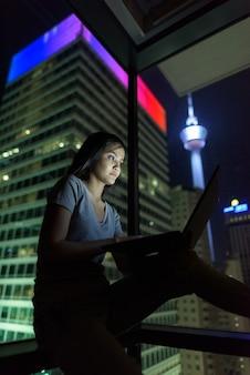 Portrait de jeune femme asiatique belle utilisant un ordinateur portable contre la fenêtre en verre avec vue sur la ville pendant la nuit