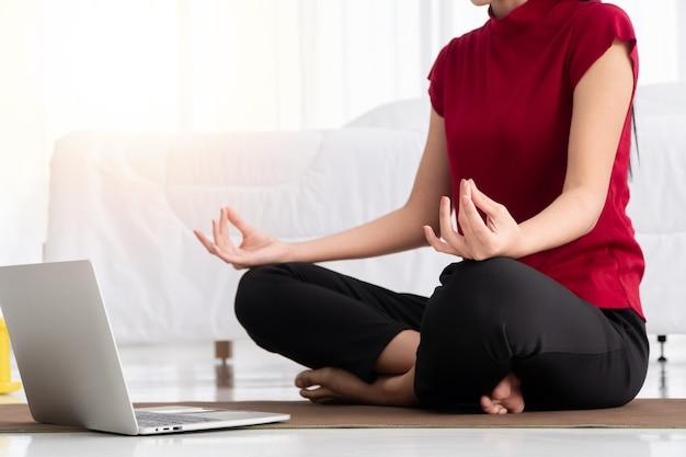 Portrait d'une jeune femme asiatique en bonne santé pratiquant des exercices de yoga assis dans la chambre et apprenant en ligne sur un ordinateur portable à la maison. concept d'exercice et de relaxation, technologie pour un nouveau mode de vie normal