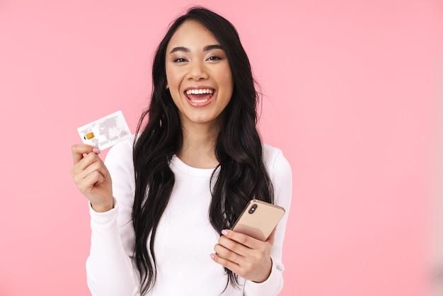 Portrait de jeune femme asiatique brune aux cheveux longs tenant un téléphone portable et une carte de crédit isolée sur un mur rose