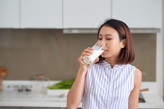 Portrait de jeune femme asiatique buvant du lait en se tenant debout dans la cuisine.