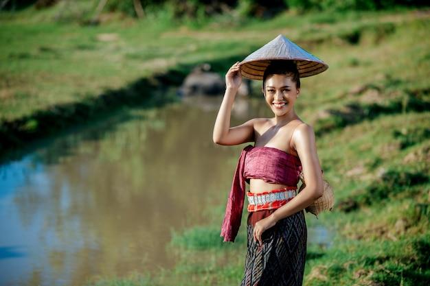 Portrait jeune femme asiatique dans de beaux vêtements traditionnels thaïlandais au champ de riz