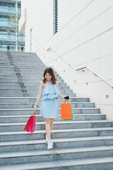 Portrait de jeune femme asiatique descendant avec un sac de couleur