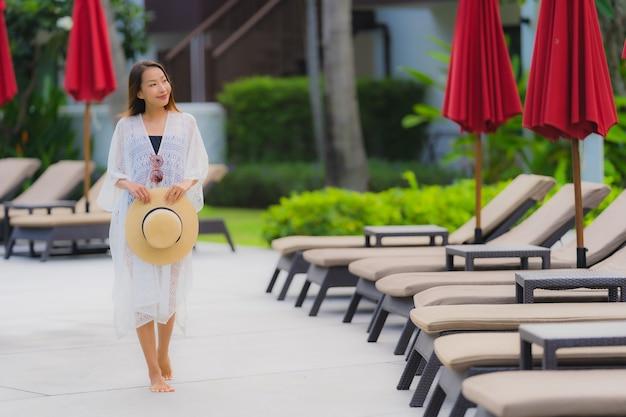 Portrait, jeune, femme asiatique, détendre, sourire, heureux, autour de, piscine extérieure, dans, hôtel, à, mer, vue océan