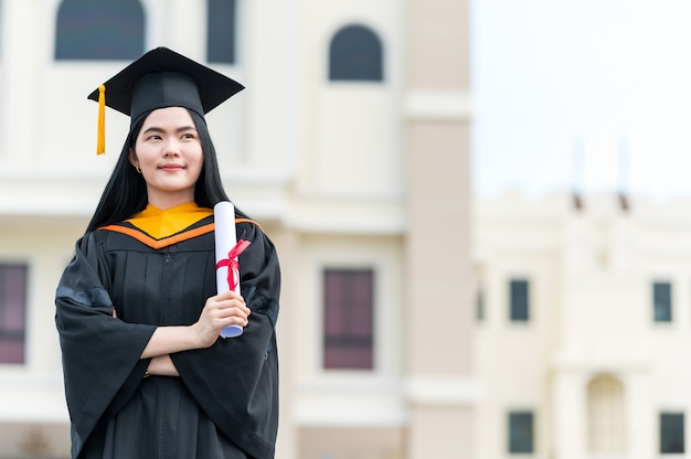 Portrait de jeune femme asiatique avec diplôme à l'extérieur