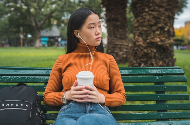 Portrait de jeune femme asiatique écoutant de la musique avec des écouteurs et tenant une tasse de café dans le parc à l'extérieur.